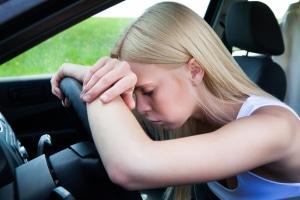 Junge Frau lehnt sich aufgrund des Elektrosmogs im Auto erschöpft aufs Lenkrad