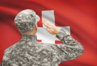 Schweizer Soldat salutiert vor der Nationalflagge